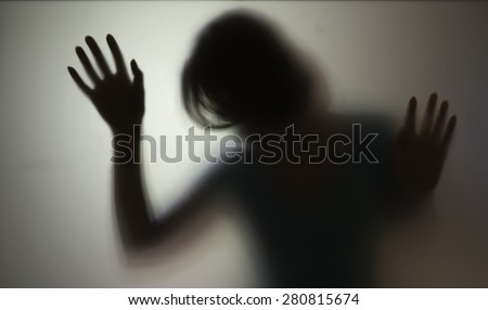 Shadowy figure behind glass  - stock photo