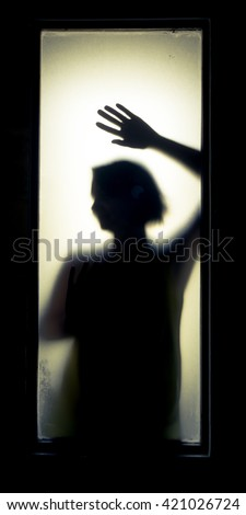 Shadowy figure behind glass.  Dramatic film grain - stock photo