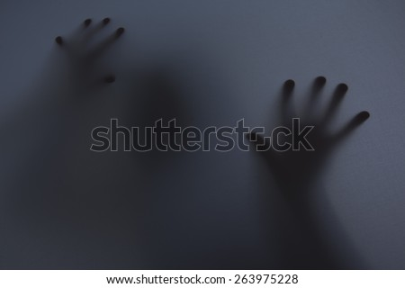 Shadowy figure behind glass / fear, panic concept