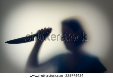 Shadowy figure of woman-killer with a knife behind glass  - stock photo