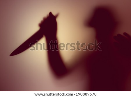 Shadowy figure with a knife behind glass  - stock photo