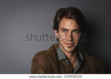 Shadowy portrait of a handsome young man with a charismatic smile on a dark grey background with copy space