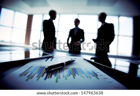 Shady image of a business team discussing the latest financial results - stock photo