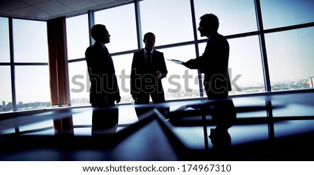 Shady image of a manager discussing business matters with his subordinates - stock photo