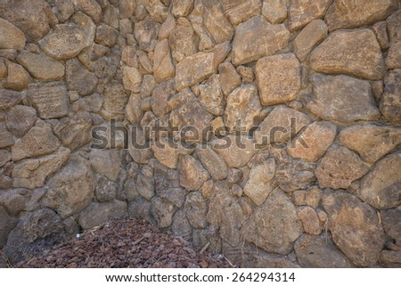 Shady Lava Wall in Old Town Honolulu with brown and black lava rocks fitted together. - stock photo