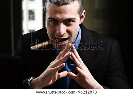 Shady man smoking a cigar in his office - stock photo