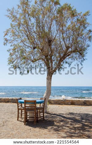 Shady place under a Salt Cedar at the Beach. Table and Chairs at the Mediterranean Sea in the Village Frangokastello  - stock photo