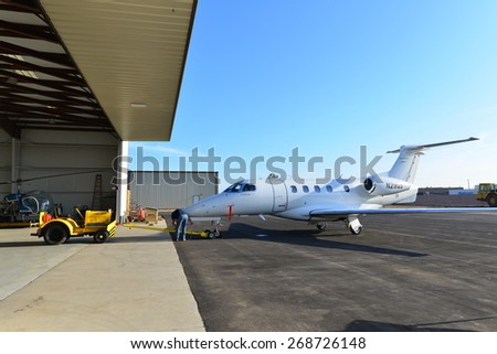 SHAFTER, CA - APR 11, 2015: An unidentified mechanic places towing gear at the nose wheel of an Embraer Phenom 300 prior to towing the corporate jet into the hangar for routine maintenance. - stock photo