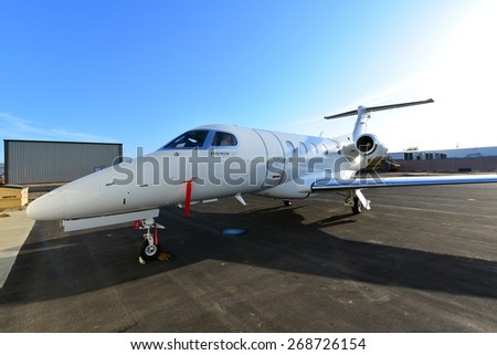 SHAFTER, CA - APR 11, 2015: This corporate jet, an Embraer Phenom 300, is parked on the ramp, ready for the hangar doors to open and routine maintenance to begin. - stock photo