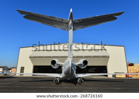 SHAFTER, CA - APR 11, 2015: This corporate jet, an Embraer Phenom 300, is parked on the ramp, ready for the hangar doors to open and routine maintenance to begin.