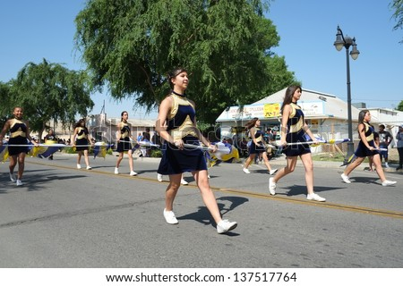 SHAFTER, CA - MAY 4: Flag waving high school girls march behind the band during the Cinco de Mayo Festival parade on May 4, 2013, at Shafter, California. - stock photo