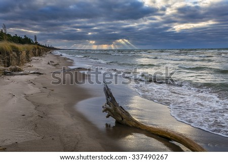 Shafts of sunlight poke out from behind autumn storm clouds on a Lake Huron beach - Pinery Provincial Park, Ontario, Canada