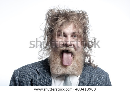 Shaggy adult gray-haired man with a beard wearing a gray suit shows tongue. Isolated - stock photo