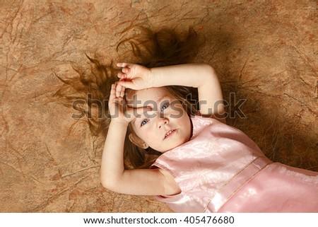Shaggy girl lying on back, top view - stock photo