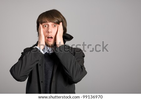 Shaken by a man in terror clutching at his head. - stock photo