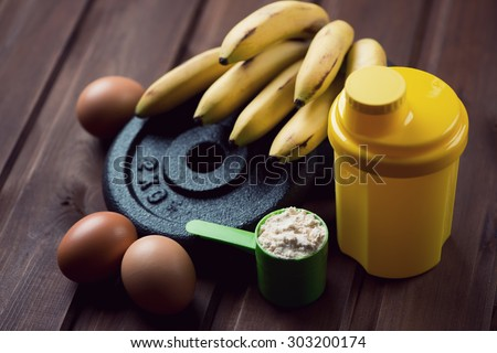 Shaker, measuring scoop with protein, eggs and bananas, close-up