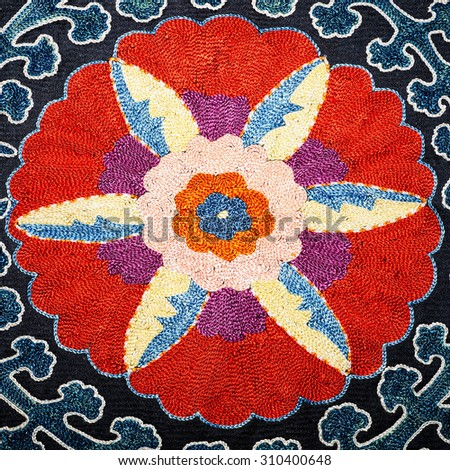 Shakhrisabz suzani colorful floral embroiddery on black silk corduroy islamic patternand the camationsin central panal  - stock photo