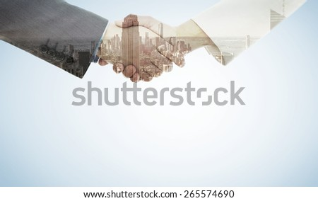 Shaking hands after business meeting against skyscraper - stock photo