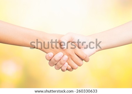 Shaking hands of two male people, on color nature background.
