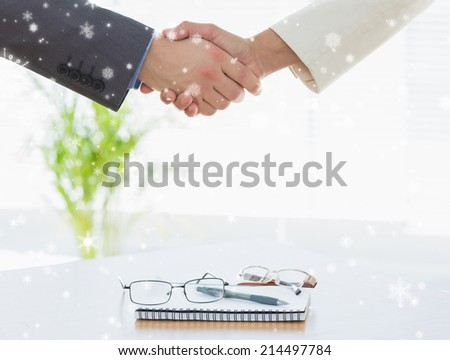 Shaking hands over eye glasses and diary after business meeting against snow falling - stock photo