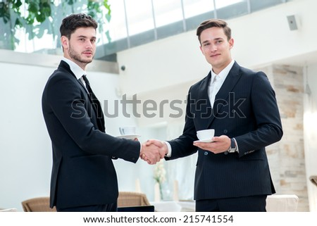 Shaking hands. Two other businessman drinking coffee and talking to each other while standing in an office and smiling to each other - stock photo