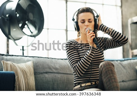 Shaking up time! Portrait of happy young woman in headphones singing into a microphone in loft apartment - stock photo