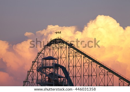 SHAKOPEE, MINNESOTA, USA - JUNE 22, 2016: The Wild Thing roller coaster and waterpark slides at Valley Fair theme park silhouetted against dramatic cumulonimbus clouds on a warm summer evening.
