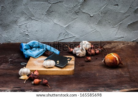 Shallots , Onion , Garlic , Chopping board and Knife on the table - stock photo