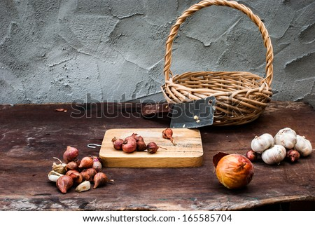 Shallots , Onion , Garlic , Chopping board and Knife with basket on the table - stock photo