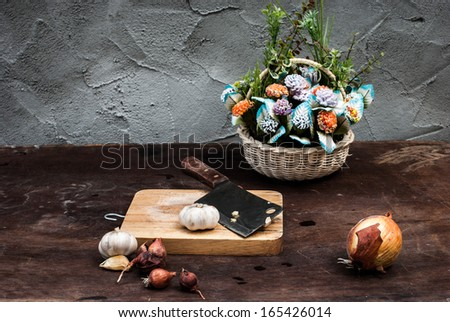 Shallots , Onion , Garlic , Chopping board and Knife with Flower on the table - stock photo