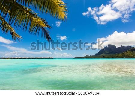 Shallow beach on the island of Bora Bora Lagoon exterior on the background of the bungalow - stock photo