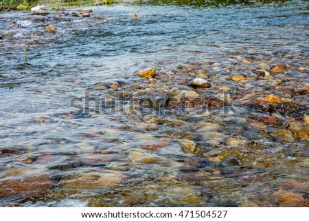 shallow clear river with colorful cobblestones