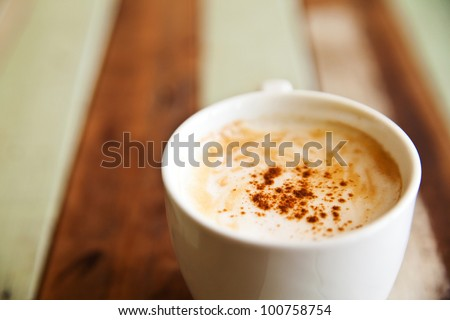 Shallow dept of field, a cup of coffee on wood background - stock photo