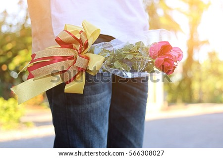 Shallow depth of field of beautiful bouquet of red roses with ribbon is held by young man with white shirt with sunshine effect on nature blurly background. lover and dating concept or Valentine's da