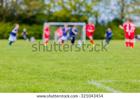 Shallow depth of field shot of young boys playing a kids european football match on green grass. - stock photo