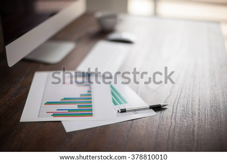 Shallow depth of field view of a businessman's workspace with a computer and some performance graphs - stock photo