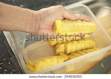 Shallow DOF authentic male hand putting sliced pineapple over plastic container