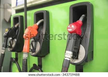 Shallow DOF of E85 nozzle hanged on vivid color gas station - stock photo