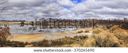 shallow lake of rain water after bushfires in Western australia. Eucalyptus forest heavily damaged in devastating fires leaving burnt outback, bush, trees, grass for recovery - stock photo