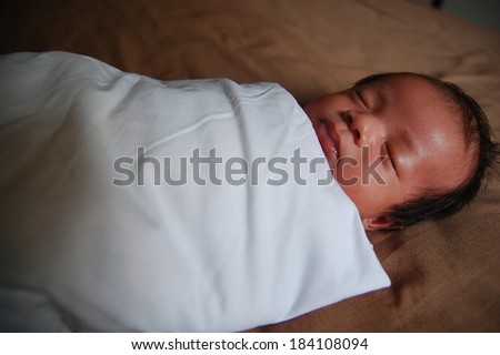 Shallow of depth newborn baby peacefully sleeping in dark light with vignette  - stock photo