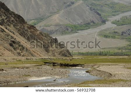 shallow river winding through mountain valley - stock photo