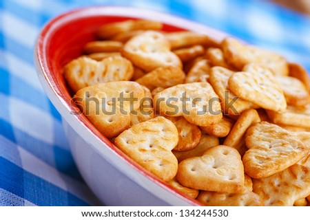 Shallow-shaped cookies heart valentine in red plate on blue tablecloth. - stock photo