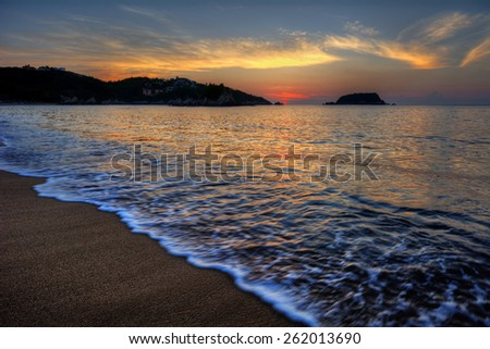 Shallow tide washing up on shore with distant cliffs under softly lit sky at dusk - stock photo