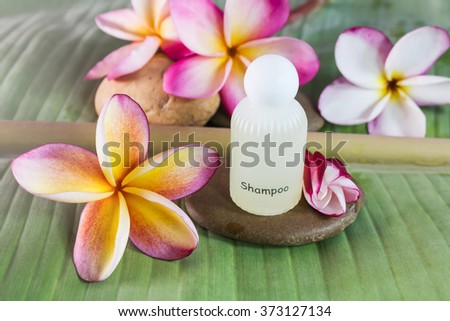 shampoo conditioner or liquid soap for bath and shower with flowers on green banana leaf - stock photo