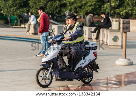 SHANGHAI - APRIL 7: policeman patrolling with electric motorcycle on people's square at the city of Shanghai in China on april 7th, 2013 - stock photo