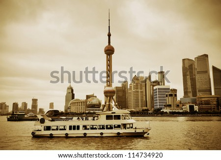Shanghai architecture over river in overcast day with boat