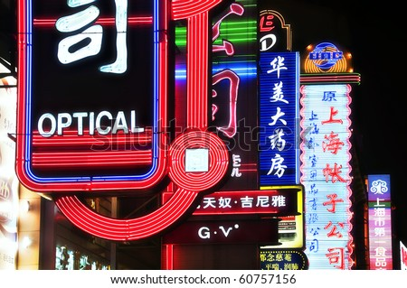 SHANGHAI - AUGUST 20: Bright neon signs along Nanjing Road, Shanghai on August 20, 2009.  Bright neon signs greet thousands of tourists who flock to Nanjing Road nightly for a walk, shopping, or drink. - stock photo