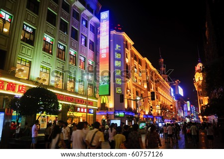 SHANGHAI - AUGUST 20: Nanjing Road on August 20, 2009 in Shanghai.  Thousands of foreign and local tourists stroll nightly under bright neon signs on Nanjing Road, Shanghai. - stock photo