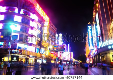 SHANGHAI - AUGUST 19: Nanjing Road on August 19, 2009 in Shanghai.  Thousands of foreign and local tourists stroll nightly under bright neon signs on Nanjing Road, Shanghai. - stock photo
