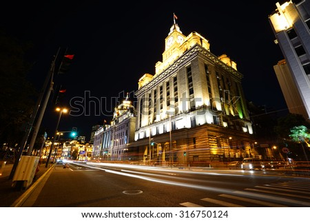 shanghai bund at night ,excellent historical buildings with vehicle trails of light on the street. - stock photo